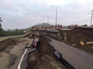 A major coastal highway torn to shreds, a crashed car visible from within a giant crack.