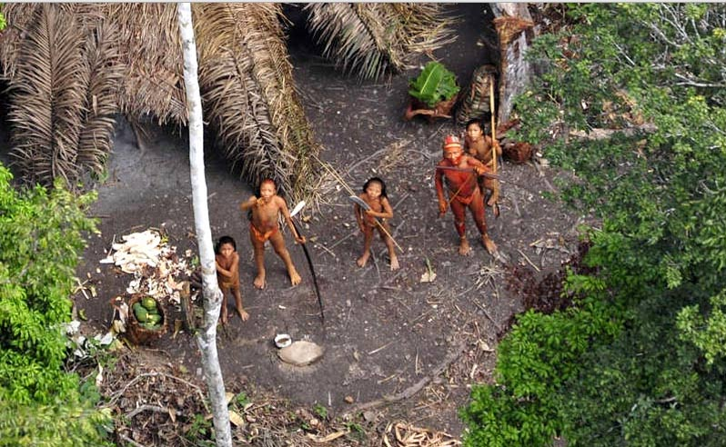 Isolated Amazon tribespeople react to a monitoring helicopter.